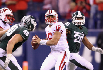 INDIANAPOLIS, IN - DECEMBER 03:  Russell Wilson #16 of the Wisconsin Badgers looks to throw a pass in the first half while under pressure against the Michigan State Spartans during the Big 10 Conference Championship Game at Lucas Oil Stadium on December 3