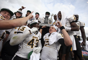 HOUSTON - DECEMBER 03:  Quarterback Austin Davis #12 (L) and Tim Green #43 and teammates of the Southern Miss Golden Eagles celebrate with the Conference USA trophy after defeating the Houston Cougars 49-28 at Robertson Stadium on December 3, 2011 in Hous