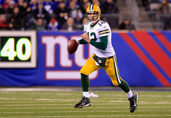 EAST RUTHERFORD, NJ - DECEMBER 04:  Aaron Rodgers #12 of the Green Bay Packers rolls out of the pocket and looks to pass in the second half against the New York Giants at MetLife Stadium on December 4, 2011 in East Rutherford, New Jersey.  (Photo by Chris