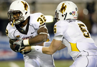 LAS VEGAS - NOVEMBER 13:  Alvester Alexander #32 of the Wyoming Cowboys takes a handoff from quarterback Austyn Carta-Samuels #5 during their game against the UNLV Rebels at Sam Boyd Stadium November 13, 2010 in Las Vegas, Nevada. UNLV won 42-16.  (Photo
