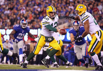 EAST RUTHERFORD, NJ - DECEMBER 04:  Aaron Rodgers #12 of the Green Bay Packers rutns to hand the ball off to Ryan Grant #25 against the New York Giants at MetLife Stadium on December 4, 2011 in East Rutherford, New Jersey.  (Photo by Al Bello/Getty Images