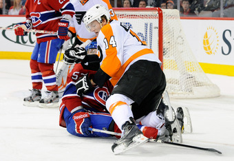 MONTREAL, CANADA - OCTOBER 26:  Sean Couturier #14 of the Philadelphia Flyers collides with Mathieu Darche #52 of the Montreal Canadiens during the NHL game at the Bell Centre on October 26, 2011 in Montreal, Quebec, Canada.  (Photo by Richard Wolowicz/Ge