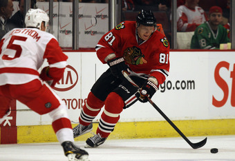 CHICAGO, IL - APRIL 10: Marian Hossa #81 of the Chicago Blackhawks controls the puck against Nicklas Lidstrom #5 of the Detroit Red Wings at the United Center on April 10, 2011 in Chicago, Illinois. The Red Wings defeated the Blackhawks 4-3. (Photo by Jon