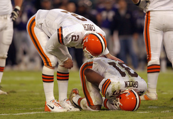 BALTIMORE - DECEMBER 22:  Tim Couch #2 of the Cleveland Browns checks on injured teammate William Green #31 against the Baltimore Ravens at Ravens Stadium on December 22, 2002 in Baltimore, Maryland. The Browns defeated the Ravens 14-13. (Photo by Doug Pe