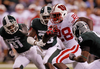 INDIANAPOLIS, IN - DECEMBER 03:  Montee Ball #28 of the Wisconsin Badgers scores his second 6-yard rushing touchdown in the first quarter against Isaiah Lewis #9 of the Michigan State Spartans during the Big 10 Conference Championship Game at Lucas Oil St