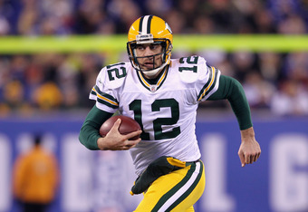 EAST RUTHERFORD, NJ - DECEMBER 04:  Aaron Rodgers #12 of the Green Bay Packers runs with the ball against the New York Giants at MetLife Stadium on December 4, 2011 in East Rutherford, New Jersey.  (Photo by Nick Laham/Getty Images)