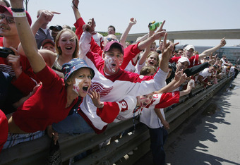 DETROIT - JUNE 17: Fans yell as a car passes with Scotty Bowman holding the Stanley Cup on Jefferson Avenue. An estimated 1 million people attended the Detroit Red Wings' Stanley Cup winning parade in Detroit, Michigan on June 17, 2002 . (Photo by Tom Pid