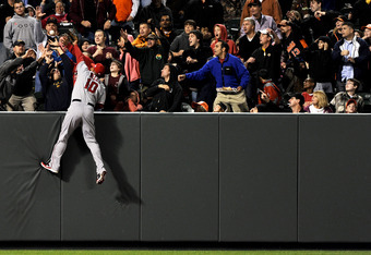 BALTIMORE, MD - SEPTEMBER 17: Vernon Wells #10 of the Los Angeles Angels of Anaheim leaps into the stands as he tries to pull back a Mark Reynolds #12 of the Baltimore Orioles (not pictured) three-shot home run in the first inning at Oriole Park at Camden