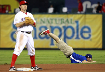 ARLINGTON, TX - OCTOBER 23: A grounds crew member performs a dance as Ian Kinsler #5 of the Texas Rangers stands on the field during Game Four of the MLB World Series against the St. Louis Cardinals at Rangers Ballpark in Arlington on October 23, 2011 in