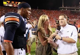 AUBURN, AL - SEPTEMBER 18:  Quarterback Cameron Newton #2 of the Auburn Tigers waits as Erin Andrews finishes her interview with head coach Gene Chizik after their 27-24 overtime win over the Clemson Tigers at Jordan-Hare Stadium on September 18, 2010 in