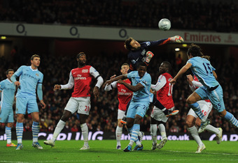 LONDON, ENGLAND - NOVEMBER 29:  Goalkeeper Lukasz Fabianski of Arsenal attempts to punch the ball clear during the Carling Cup Quarter Final match between Arsenal and Manchester City at Emirates Stadium on November 29, 2011 in London, England.  (Photo by