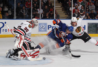 UNIONDALE, NY - DECEMBER 08: Ray Emery #30 and defenseman Niklas Hjalmarsson #4 of the Chicago Blackhawks defend against John Tavares #91 of the New York Islanders at the Nassau Veterans Memorial Coliseum on December 8, 2011 in Uniondale, New York.  (Phot