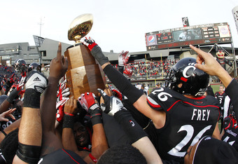 CINCINNATI, OH - DECEMBER 03: Drew Frey #26 of the Cincinnati Bearcats reaches for the Big East Championship trophy while celebrating with teammates after the Bearcats defeated the Connecticut Huskies 35-27 to claim their share of the 2011 Big East Champi