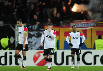 BASEL, SWITZERLAND - DECEMBER 07:  Rio Ferdinand , Wayne Rooney and Patrice Evra  of Manchester United walks dejected after Basel scored their second goal during the UEFA Champions League Group C match between FC Basel 1893 and Manchester United at St. Ja