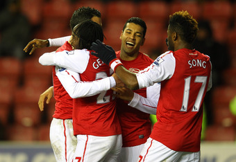 WIGAN, ENGLAND - DECEMBER 03:  Gervinho of Arsenal celebrates with Robin Van Persie and Andre Santos after scoring the third goal during the Barclays Premier League match between Wigan Athletic and Arsenal at the DW Stadium on December 3, 2011 in Wigan, E