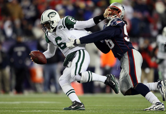 FOXBORO, MA - DECEMBER 06:  Mark Sanchez #6 of the New York Jets attempts to escape the pass rush of Jermaine Cunningham #96 of the New England Patriots at Gillette Stadium on December 6, 2010 in Foxboro, Massachusetts.  (Photo by Elsa/Getty Images)