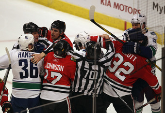 CHICAGO, IL - APRIL 19: Referees try to break up a fight between members of the Chicago Blackhawks including Ryan Johnson #17, Chris Campoli #14 and John Scott #32 with members of the Vancouver Canucks including Jannik Hansen #36, Maxim Lapierre #40 and T