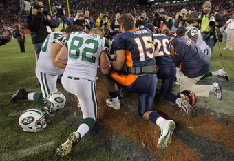 DENVER, CO - NOVEMBER 17:  Quarterback Tim Tebow #15 of the Denver Broncos kneels with teammates and members of the New York Jets at midfield for prayer following the game at Sports Authority Field at Mile High on November 17, 2011 in Denver, Colorado. Te
