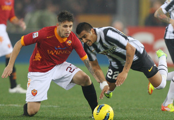 ROME, ITALY - DECEMBER 12:  Aleandro Greco (L) of AS Roma competes for the ball with Arturo Vidal of Juventus FC during the Serie A match between AS Roma and Juventus FC at Stadio Olimpico on December 12, 2011 in Rome, Italy.  (Photo by Paolo Bruno/Getty