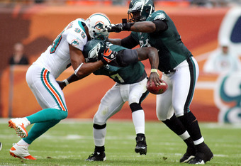 MIAMI GARDENS, FL - DECEMBER 11:  Defensive end Jason Taylor #99 (L) of the Miami Dolphins sacks Quarterback Michael Vick #7 (C) of the Philadelphia Eagles at Sun Life Stadium on December 11, 2011 in Miami Gardens, Florida.  (Photo by Marc Serota/Getty Im