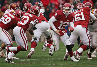 NORMAN, OK - NOVEMBER 26:  Quarterback Landry Jones #12 of the Oklahoma Sooners looks to hand off to running back Brandon Williams #23 during the first half against the Iowa State Cyclones on November 26, 2011 at Gaylord Family-Oklahoma Memorial Stadium i