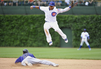 CHICAGO, IL - JUNE 27:  Jonathan Herrera #18 of the Colorado Rockies slides into second base as shortstop Starlin Castro #13 of the Chicago Cubs leaps for a wild throw from catcher Geovany Soto #18 during the sixth inning at Wrigley Field on June 27, 2011