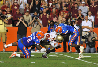 GAINESVILLE, FL - NOVEMBER 26:  Linebacker Telvin Smith #22 of the Florida State Seminoles breaks through a block of center Jonotthan Harrison #72 to tackle running back Chris Rainey #1 of the Florida Gators November 26, 2011 at Ben Hill Griffin Stadium i