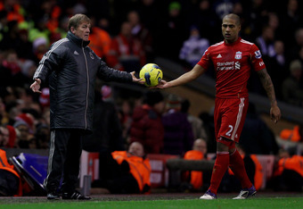 LIVERPOOL, ENGLAND - DECEMBER 10:  Liverpool Manager Kenny Dalglish passes the ball to Glen Johnson during the Barclays Premier League match between Liverpool and Queens Park Rangers at Anfield on December 10, 2011 in Liverpool, England.  (Photo by Clive