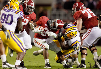 TUSCALOOSA, AL - NOVEMBER 05:  Bennie Logan #93 of the LSU Tigers tackles Trent Richardson #3 of the Alabama Crimson Tide during the second half of the game at Bryant-Denny Stadium on November 5, 2011 in Tuscaloosa, Alabama.  (Photo by Kevin C. Cox/Getty