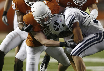 AUSTIN, TX - SEPTEMBER 10:  Running back J.J. Di Luigi #10 of the BYU Cougars is stopped in the fourth quarter by Texas Longhorn defenders safety Nolan Brewster #7, cornerback Carrington Byndom #23, and safety Blake Gideon #21 on September 10, 2011 at Dar