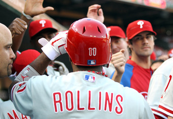 ST LOUIS, MO - OCTOBER 05:  Jimmy Rollins #11 of the Philadelphia Phillies is greeted by his teammates in the dugout after scoring on a Chase Utley #26 triple in the first inning against the St. Louis Cardinals in Game Four of the National League Division