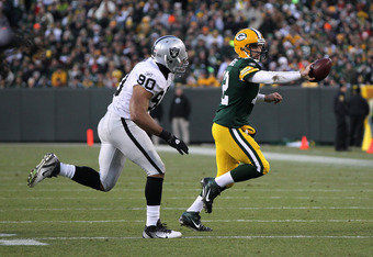 GREEN BAY, WI - DECEMBER 11: Aaron Rodgers #12 of the Green Bay Packers flips the ball as Desmond Bryant #90 of the Oakland Raiders closes in at Lambeau Field on December 11, 2011 in Green Bay, Wisconsin. The Packers defeated the Raiders 46-16. (Photo by