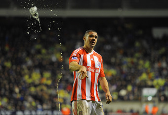 WOLVERHAMPTON, ENGLAND - DECEMBER 17: Jonathan Walters of Stoke tosses a bottle, which was thrown onto the pitch after the 2nd Stoke goal, during the Barclays Premier League match between  Wolverhampton Wanderers and Stoke City at Molineux on December 17,