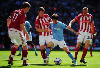 LONDON, ENGLAND - MAY 14:  David Silva (2nd right) of Manchester City is challenged by Ryan Shawcross (L),  during the FA Cup sponsored by E.ON Final match between Manchester City and Stoke City at Wembley Stadium on May 14, 2011 in London, England. (Phot