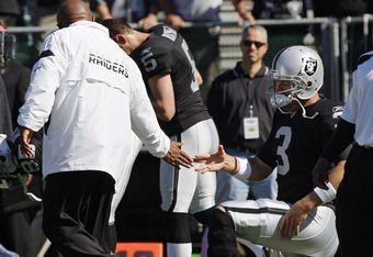 OAKLAND, CA - OCTOBER 23: Head coach Hue Jackson of the Oakland Raiders slaps hands with quarterback Carson Palmer #3 before a game against the Kansas City Chiefs on October 23, 2011 at O.co Coliseum in Oakland, California. The Chiefs won 28-0. (Photo by