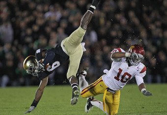 SOUTH BEND, IN - OCTOBER 22:  Hayes Pullard #10 of the University of Southern California Trojans upends Theo Riddick #6 of the Notre Dame Fighting Irish at Notre Dame Stadium on October 22, 2011 in South Bend, Indiana. USC defeated Notre Dame 31-17.  (Pho