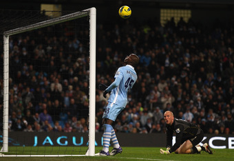 MANCHESTER, ENGLAND - DECEMBER 03:  Mario Balotelli of Manchester City about to score the fourth goal as Norwich City keeper John Ruddy watches during the Barclays Premier League match between Manchester City and Norwich City at Etihad Stadium on December