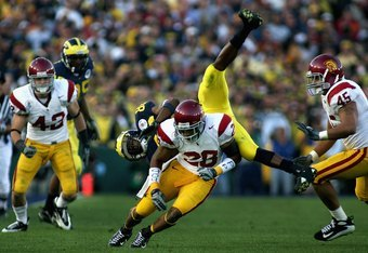 PASADENA, CA - JANUARY 01:  Mario Manningham #86 of the Michigan Wolverines is tackled by Terrell Thomas #28 of the USC Trojans during the Rose Bowl game on January 1, 2007 at the Rose Bowl in Pasadena, California. The Trojans defeated the Wolverines 32-1