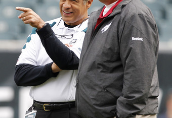 PHILADELPHIA, PA - NOVEMBER 13:   Defensive Coordinator Juan Castillo, left, of the Philadelphia Eagles talks with Assistant Head Coach Russ Grimm of the Arizona Cardinals before the start of their game at Lincoln Financial Field on November 13, 2011 in P