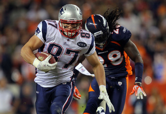 DENVER, CO - DECEMBER 18:  Tight end Rob Gronkowski #87 of the New England Patriots runs with the ball against free safety Quinton Carter #28 the Denver Broncos at Sports Authority Field at Mile High on December 18, 2011 in Denver, Colorado.  (Photo by Do