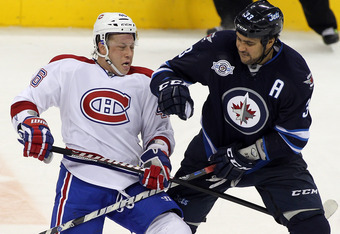 WINNIPEG, CANADA - DECEMBER 22: Dustin Byfuglien #33 of the Winnipeg Jets and Andrei Kostitsyn #46 of the Montreal Canadiens collide in NHL action at the MTS Centre on December 22, 2011 in Winnipeg, Manitoba, Canada. (Photo by Marianne Helm/Getty Images)