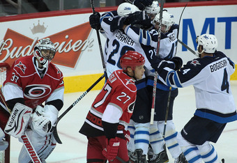 WINNIPEG, CANADA - SEPTEMBER 28: Evander Kane #9 of the Winnipeg Jets is swarmed by teammates while goalie Brian Boucher #33 looks dejected after Kane scored a third period goal against of the Carolina Hurricanes in preseason NHL action at the MTS Centre