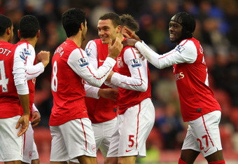 WIGAN, ENGLAND - DECEMBER 03:  Thomas Vermaelen of Arsenal celebrates with Mikel Arteta and Gervinho after scoring the second goal during the Barclays Premier League match between Wigan Athletic and Arsenal at the DW Stadium on December 3, 2011 in Wigan,
