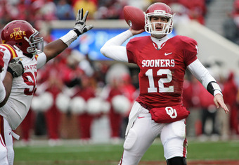 NORMAN, OK - NOVEMBER 26:  Quarterback Landry Jones #12 of the Oklahoma Sooners looks to throw under pressure in the first half on November 26, 2011 at Gaylord Family-Oklahoma Memorial Stadium in Norman, Oklahoma. Oklahoma leads Iowa State 23-6 at the hal