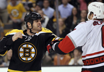 BOSTON, MA - OCTOBER 18:  Nathan Horton #18 of the Boston Bruins and Tim Gleason #6 of the Carolina Hurricanes fight in the third period on October 18, 2011 at TD Garden in Boston, Massachusetts. The Carolina Hurricanes defeated the Boston Bruins 4-1.  (P