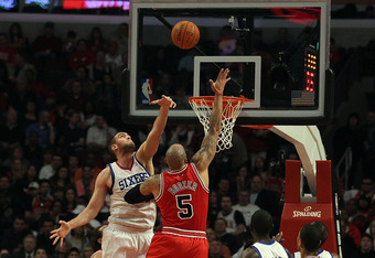 CHICAGO, IL - MARCH 28: Carlos Boozer #5 of the Chicago Bulls puts up a shot against Spencer Hawes #00 of the Philadelphia 76ers at the United Center on March 28, 2011 in Chicago, Illinois. NOTE TO USER: User expressly acknowledges and agrees that, by dow