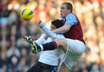 BIRMINGHAM, ENGLAND - DECEMBER 18: Richard Dunne of Villa in action with Luis Suarez of Liverpool during the Barclays Premier league match between Aston Villa and Liverpool at Villa Park on December 18, 2011 in Birmingham, England.  (Photo by Michael Rega