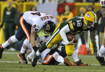 GREEN BAY, WI - DECEMBER 25: Aaron Rodgers #12 of the Green Bay Packers runs the ball and is tackled by Brian Urlacher #54 of the Chicago Bears on December 25, 2011 at Lambeau Field in Green Bay, Wisconsin.  (Photo by David Banks/Getty Images)