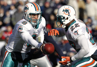 FOXBORO, MA - DECEMBER 24:  Matt Moore #8 of the Miami Dolphins hands the ball off to Reggie Bush #22 during the first quarter against the New England Patriots at Gillette Stadium on December 24, 2011 in Foxboro, Massachusetts.  (Photo by Winslow Townson/
