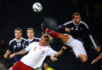 GLASGOW, SCOTLAND - AUGUST 10: Phil Bardsley of Scotland clears the ball under pressure from Simon Kjaer of Denmark during the International Friendly Match between Scotland and Denmark at Hampden Park on August 10, 2011 in Glasgow, Scotland.  (Photo by La